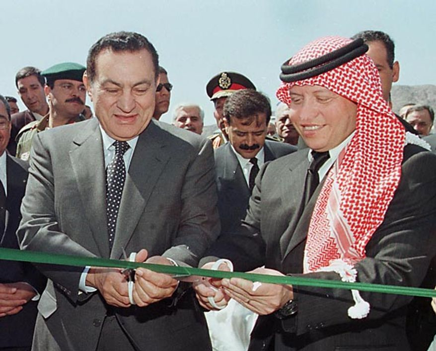 Jordan's King Abdullah II, right, and Egyptian President Hosni Mubarak cut a green ribbon to officially linking the two countries' electric grids in Taba, Jordan, on Tuesday March 16, 1999. ( AP Photo/Pool)