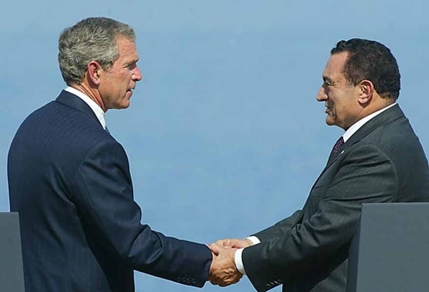 President George W. Bush shakes hands with Egyptian President Hosni Mubarak, right, during a Multilateral Summit in Sharm el Sheik, Egypt, on June 3, 2003. (AP Photo/Pablo Martinez Monsivais, File)
