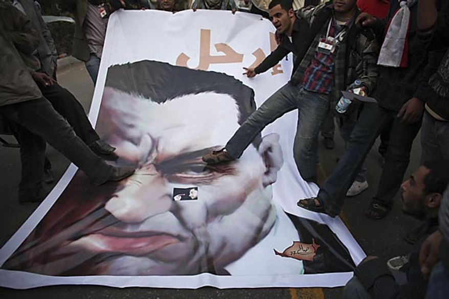 Anti-government protesters stamp on a poster of Egyptian President Hosni Mubarak as they pose for a photo outside the Egyptian parliament in Cairo on Feb. 9, 2011. (AP Photo/Tara Todras-Whitehill, File