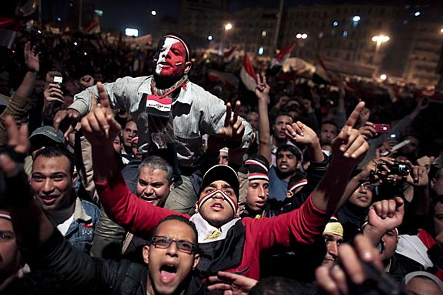 Egyptians celebrate the news of the resignation of President Hosni Mubarak, who handed control of the country to the military, at night in Tahrir Square in downtown Cairo, Egypt Friday, Feb. 11, 2011. (AP Photo/Tara Todras-Whitehill)