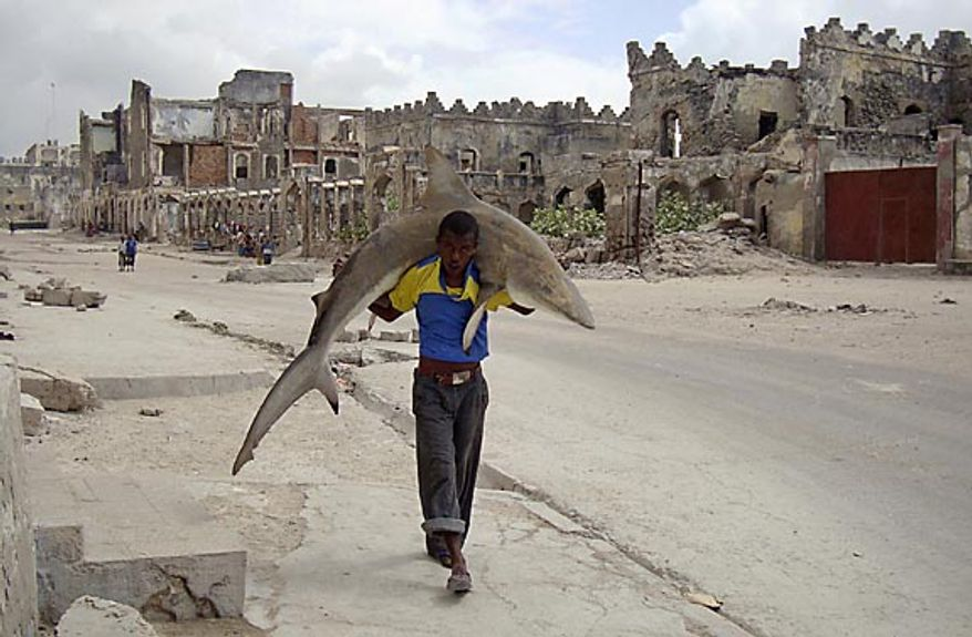 In this photo provided by World Press Photo, the 1st Prize Daily Life Single of the 2011 World Press Photo Contest by Omar Feisal, Somalia, Reuters, shows a man carrying a shark through the streets of Mogadishu, Somalia, Sept. 23, 2010. (AP Photo/Omar Feisal/Reuters)