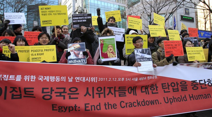 Members of Amnesty International in South Korea shout slogans during a rally in Seoul, South Korea, to express their support to the Egyptians who forced the resignation of President Hosni Mubarak, after ruling Egypt for 30 years, on Saturday, Feb. 12, 2011. (AP Photo/ Lee Jin-man)