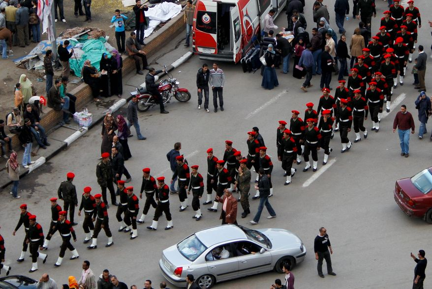 Associated Press Egyptian army officers walk among cars and protesters Sunday in Tahrir Square in Cairo. Egypt's military is taking down the makeshift tents of protesters in an effort to allow traffic flow to return to normal for the first time in weeks.