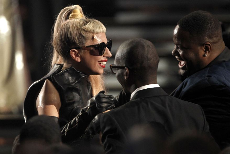 Lady Gaga is congratulated as she wins the award for best pop vocal album at the 53rd annual Grammy Awards on Sunday, Feb. 13, 2011, in Los Angeles. (AP Photo/Matt Sayles)