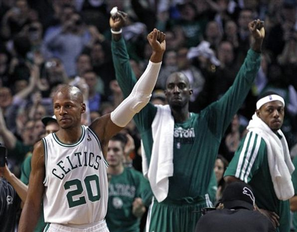 Boston Celtics' Ray Allen (20) acknowledges the crowd after hitting a 3-pointer against the Los Angeles Lakers to break the NBA record for 3-point baskets, during the first quarter of a basketball game in Boston on Thursday, Feb. 10, 2011. In back are teammates Kevin Garnett, center, and Paul Pierce, right. (AP Photo/Elise Amendola)
