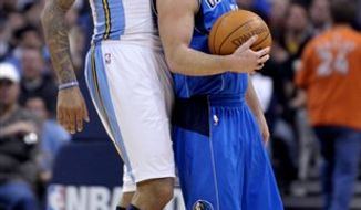 Denver Nuggets' Carmelo Anthony (15) scores against Dallas Mavericks Tyson Chandler, right, in the closing seconds of the first quarter of an NBA basketball game in Denver on Thursday, Feb. 10, 2011. (AP Photo/Joe Mahoney)