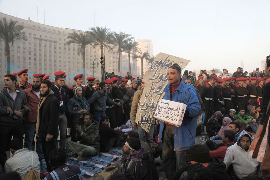 Egyptian soldiers surround the remaining protesters on Tahrir Square in Cairo on Sunday, Feb. 13, 2011, as the military tries to help people return to normal life. Protesters were debating whether to close down their 24-hour-a-day demonstration camp in their square. (AP Photo/Manoocher Deghati)