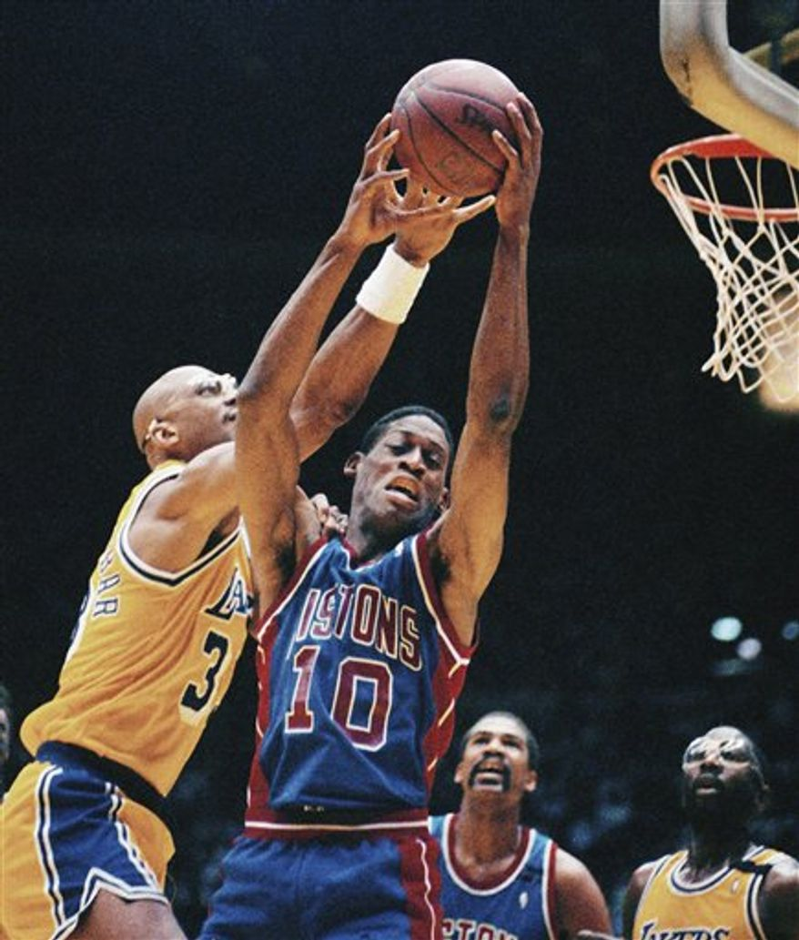FILE - In this June 11, 1989 file phot, Detroit Pistons' Dennis Rodman (10) grabs a rebound away from Los Angeles Lakers' Kareem Abdul-Jabbar, left, during Game 3 of the NBA Finals in Los Angeles. The Pistons plan to retire Rodman's No. 10 during a halftime ceremony later this season. Rodman, the eccentric rebounding specialist who helped the Pistons win NBA titles in 1989 and 1990, will be honored April 1 when the Pistons host the Chicago Bulls, a team Rodman won three championships with from 1996-98. (AP Photo/Bob Galbraith, File)
