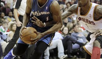 Washington Wizards' Nick Young, left, is fouled by Cleveland Cavaliers' Daniel Gibson in the first quarter in an NBA basketball game Sunday, Feb. 13, 2011, in Cleveland. (AP Photo/Tony Dejak)