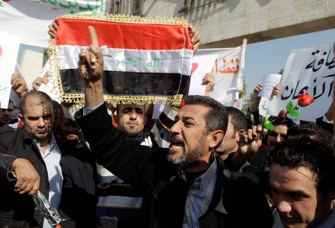 Protesters chant anti-government slogans during a demonstration in Baghdad on Monday. Hundreds of Iraqis rallied in central Baghdad against corruption and the lack of government services. (Associated Press)