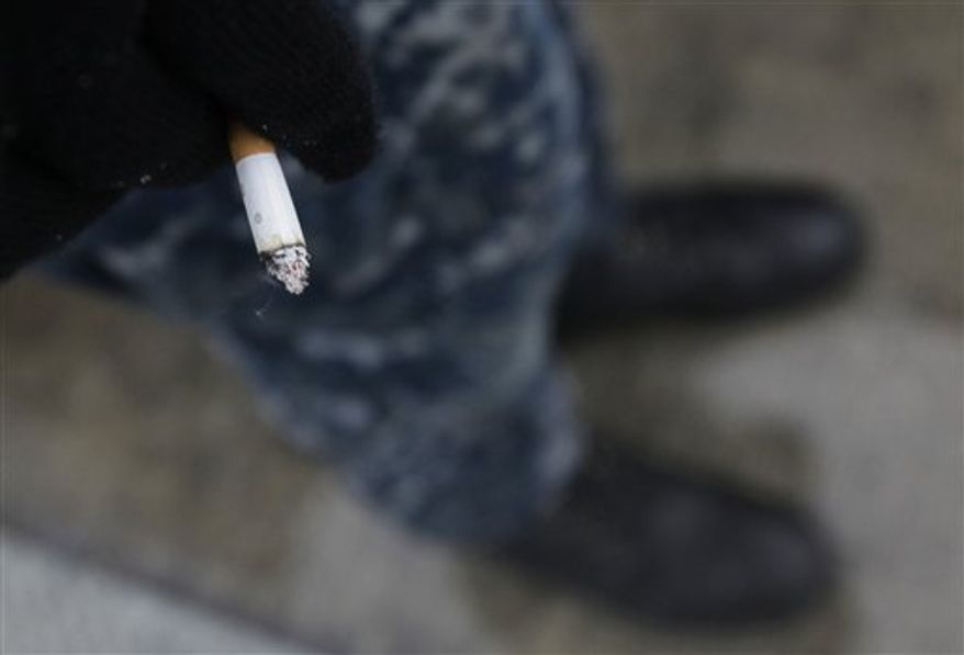 In this photo taken Friday, Feb. 11, 2011, a crew member from the USS Charlotte, a nuclear powered attack submarine, stands on a dock to smoke a cigarette at the Yokosuka Naval Base, south of Tokyo. As of January all submarines in the U.S. Navy are officially smoke free, and it's been a tense transition. (AP Photo/Greg Baker)