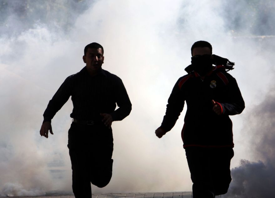Bahraini demonstrators run from tear gas on Monday as riot police disperse a protest in the village of Duraz, Bahrain, outside the capital of Manama. Demonstrations broke out nationwide in response to calls on social media sites for major anti-government protests and were dispersed by riot police firing tear gas and chasing demonstrators. (Associated Press)