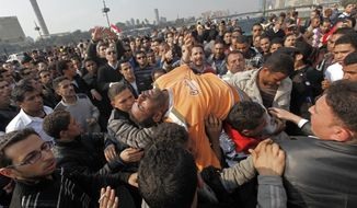 A man is taken away after he fainted during a scuffle with policemen that were protesting in Tahrir Saquare in Cairo, Egypt, Monday Feb. 14, 2011. (AP Photo/Hussein Malla)