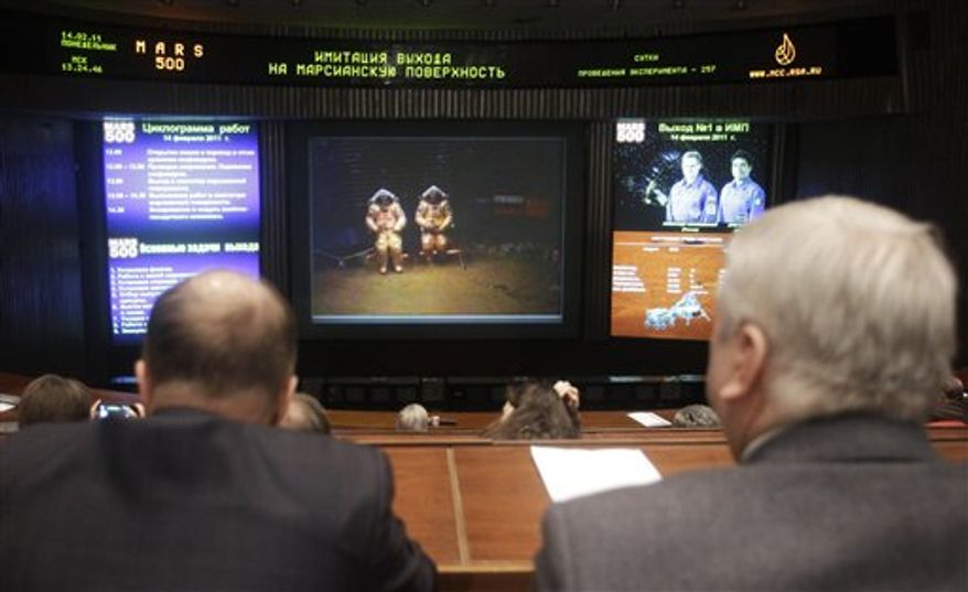 Russian space officials watch video footage of researchers in space suits simulating a landing on Mars at the Mission Control Center in Korolyov, just outside Moscow, Monday, Feb. 14, 2011. The international crew of researchers conducted a mock landing on Mars after 257 days of confinement in an isolated module to imitate a flight to the Red Planet. (AP Photo/Sergey Ponomarev)
