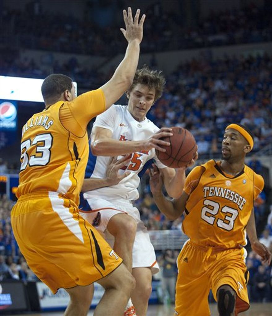 Florida's Chandler Parsons (25) holds the ball in between Tennessee's Brian Williams (33) and Cameron Tatum (23) in the first half of a NCAA college basketball game in Gainesville, Fla., Saturday, Feb. 12, 2011. Florida defeated Tennessee 61-60. (AP Photo/Phil Sandlin)