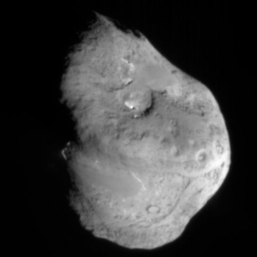 This photo released by NASA/JPL on Feb. 15, 2011 shows an image from NASA's Stardust mission of comet Tempel 1 taken on Feb. 14, 2011. The Stardust craft zipped past a comet half the size of Manhattan during a Valentine's Day rendezvous that scientists hoped would shed light on these icy solar system bodies. At nearest approach, the craft passed within 112 miles of the potato-shaped comet, closer than the original prediction. (AP Photo/ NASA/JPL/ Caltech/Cornell)