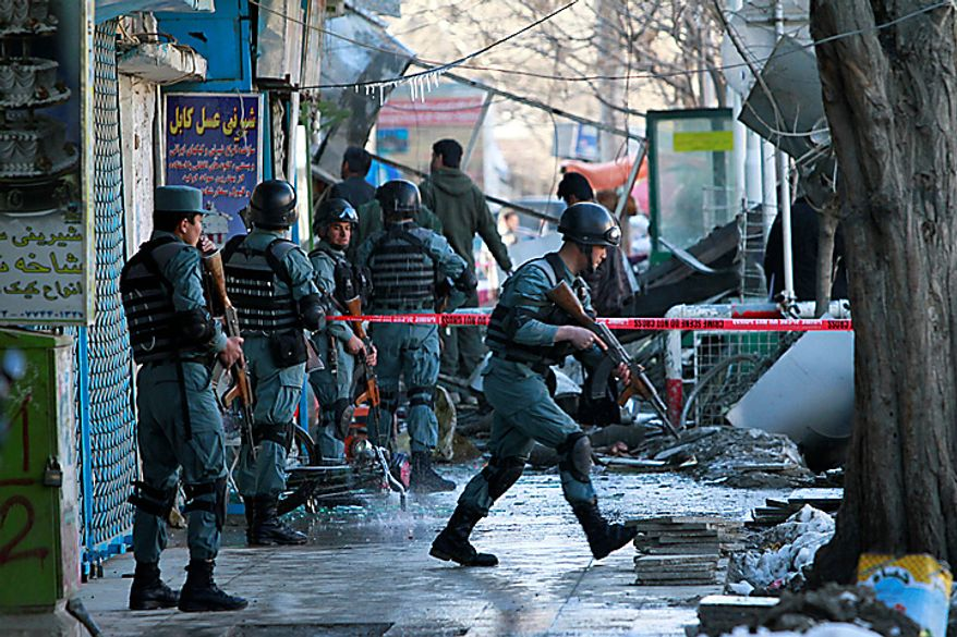 Afghan police take up positions as they arrive near the site of suicide bombing in Kabul, Afghanistan, on Monday, Feb. 14, 2011. The explosion rocked a shopping and hotel complex and killed at least two people, officials said, in the second attack in less than a month in the heavily secured Afghan capital. (AP Photo/Dar Yasin)