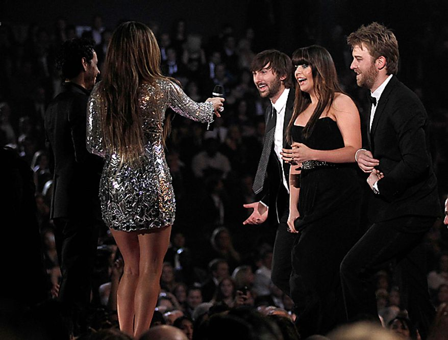From left, Marc Anthony and Jennifer Lopez present Lady Antebellum with the award for best record of the year at the 53rd annual Grammy Awards on Sunday, Feb. 13, 2011, in Los Angeles. From right are, Charles Kelley, Hillary Scott and Dave Haywood. (AP Photo/Matt Sayles)