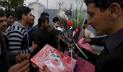 """A Pakistani police officer receives flowers and Valentine's Day cards for Mumtaz Qadri, the confessed killer of a liberal Pakistani governor, given by students during a rally outside the Adiala Jail, where Qadri's special court hearing was held on Monday, Feb. 14, 2011, in Rawalpindi, Pakistan. Qadri pleaded guilty to murder, telling a judge he didn't regret gunning the politician down because he killed """"an apostate,"""" as required under his interpretation of Islamic law, lawyers said. (AP Photo/Anjum Naveed)"""
