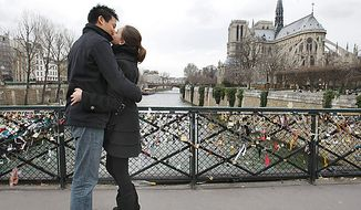 French lovers David, 22, and Charlene, 23, share a Valentine's Day kiss near Notre-Dame Cathedral in Paris on Monday, Feb. 14, 2011. The padlocks on the fence of the bridge belong to lovers who throw the keys to the locks into the Seine as a symbol of enduring love. (AP Photo/Jacques Brinon )