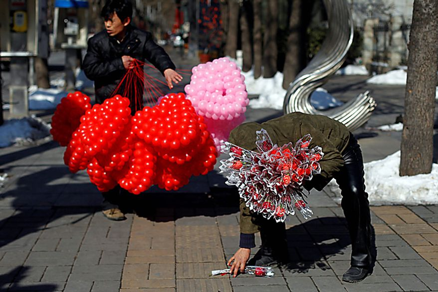 A vendor selling roses and another selling heart-shaped balloons wait for Valentine's Day customers in Beijing on Monday, Feb. 14, 2011. (AP Photo/Ng Han Guan)