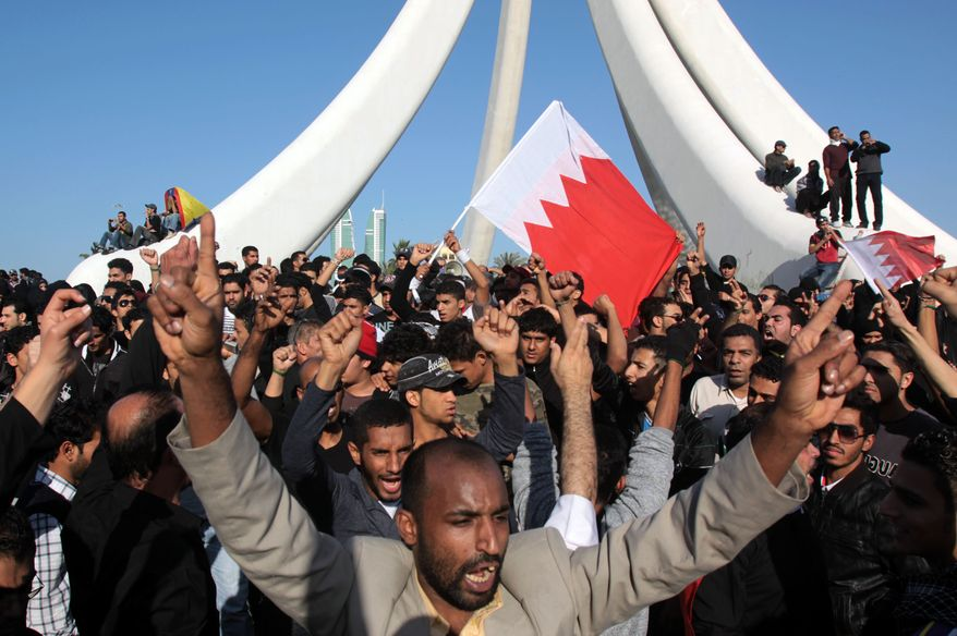 Demonstrators chant and wave Bahraini flags near the Pearl Monument on a main square in Manama, Bahrain, Tuesday Feb. 15, 2011. Thousands of protesters poured into the square in Bahrain's capital in an Egypt-style rebellion that sharply escalated pressure on authorities as the Arab push for change gripped the Gulf for the first time. (AP Photo/Hasan Jamali)