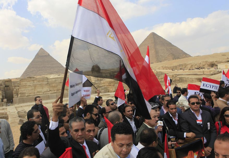 Hundreds of Egyptian tourist guides flash welcoming banners in different languages as a message to tourists during a march in front of the historical site of Giza Pyramids, Egypt, Monday, Feb.14, 2011. (AP Photo/Amr Nabil)