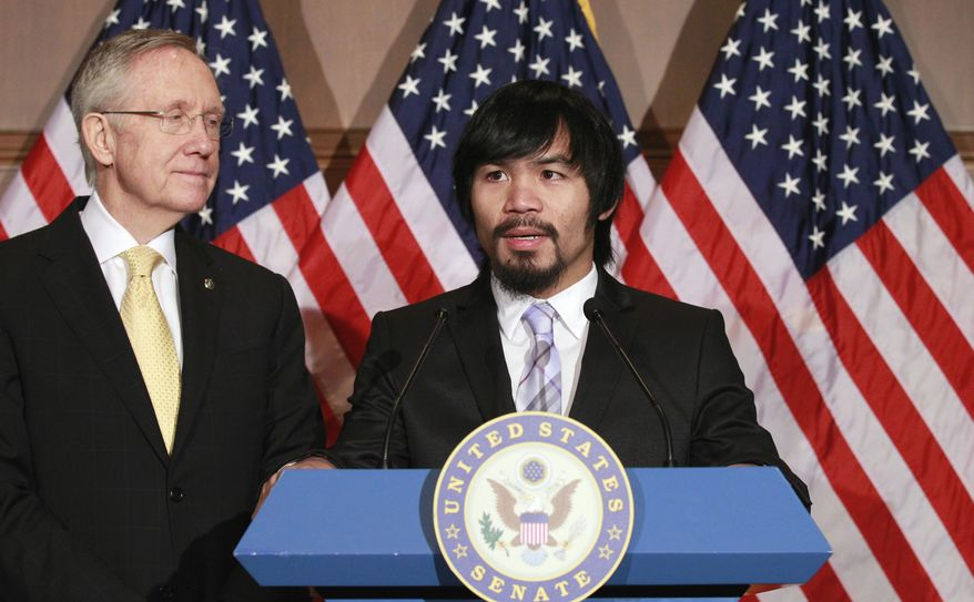 Senate Majority Leader Harry Reid of Nev. listens at left as Filipino Congressman and eight-term world champion boxer Manny Pacquiao speaks on Capitol Hill in Washington, Tuesday, Feb. 15, 2011. (AP Photo/Alex Brandon)