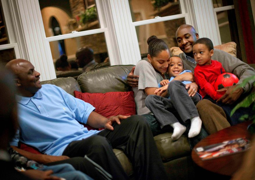 Shelton Haynes (far right) sits Tuesday with wife Tiisha, and sons Jamir, 2 (right) and Jayden, 4, while visiting with his father, Cleveland Haynes Jr. (left), at his home in Duluth, Ga. The younger Mr. Haynes moved his family to Atlanta after growing up in New York City. (Associated Press)