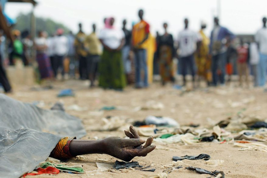 The body of a man killed by gunfire lies covered in a side street of Abidjan, Ivory Coast, on Jan. 11. The Associated Press has obtained records from four of nine morgues that provide proof of mass killings after the Nov. 28 national election. (Associated Press)