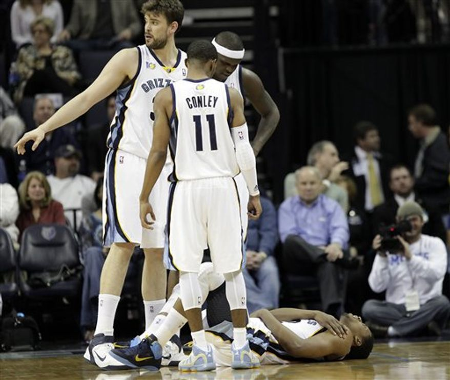 Memphis Grizzlies forward Rudy Gay (22) is helped off the court by head athletic trainer Drew Graham and Hasheem Thabeet after he suffered a left shoulder subluxation while playing against the Philadelphia 76ers during the second quarter of an NBA basketball game in Memphis, Tenn., Tuesday, Feb. 15, 2011. The Grizzlies won 102-91. (AP Photo/Lance Murphey)