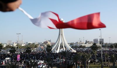 A demonstrator waves a Bahraini flag Tuesday on a highway overpass overlooking the Pearl Monument, centered on a main square, in Manama, Bahrain. Thousands of protesters poured into the square in the capital in an Egypt-style rebellion that sharply escalated pressure on authorities as the Arab push for change gripped the Gulf for the first time. (Associated Press)