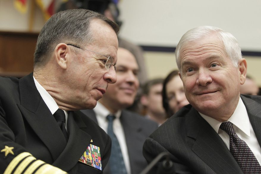 Defense Secretary Robert Gates, right, talks with Joint Chiefs Chairman Adm. Michael Mullen on Capitol Hill in Washington on Wednesday, Feb. 16, 2011, as they testified before the House Armed Services Committee. (AP Photo/J. Scott Applewhite)