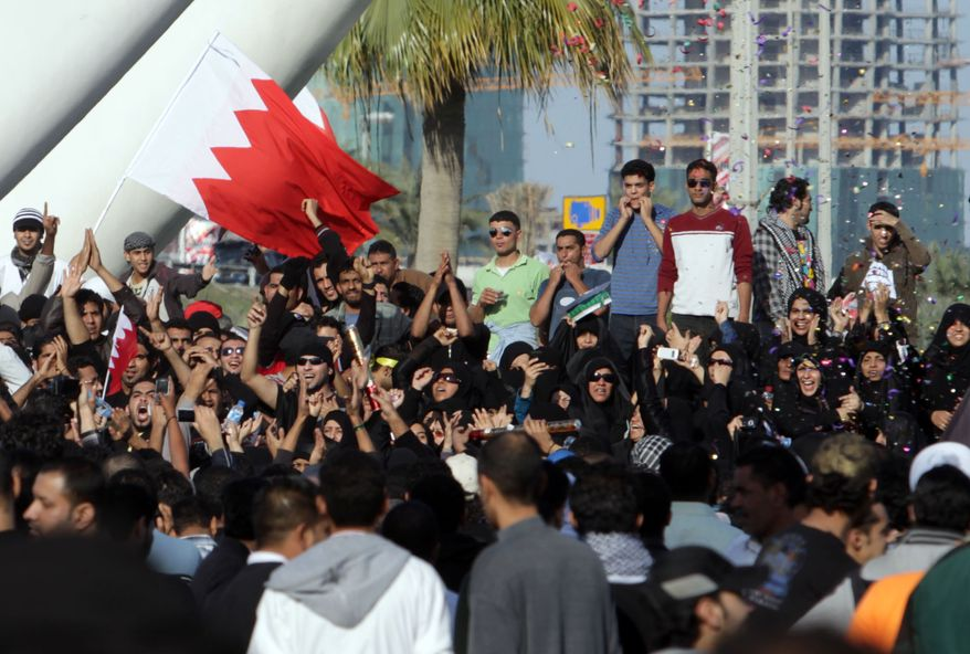 Demonstrators wave Bahraini flags, cheer and throw confetti under the Pearl Monument on a main square in Manama, Bahrain, on Tuesday, Feb. 15, 2011. Thousands of protesters poured into the square in an Egypt-style rebellion that sharply escalated pressure on authorities as the Arab push for change gripped the Gulf for the first time. (AP Photo/Hasan Jamali)