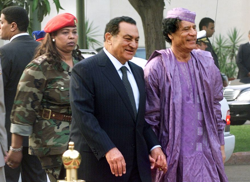 ** FILE ** Egyptian President Hosni Mubarak (center) welcomes Libyan leader Moammar Gadhafi (right), who is guarded by a female bodyguard (left), upon his arrival at the Presidential Palace in Cairo in July 2002. (AP Photo/Amr Nabil)