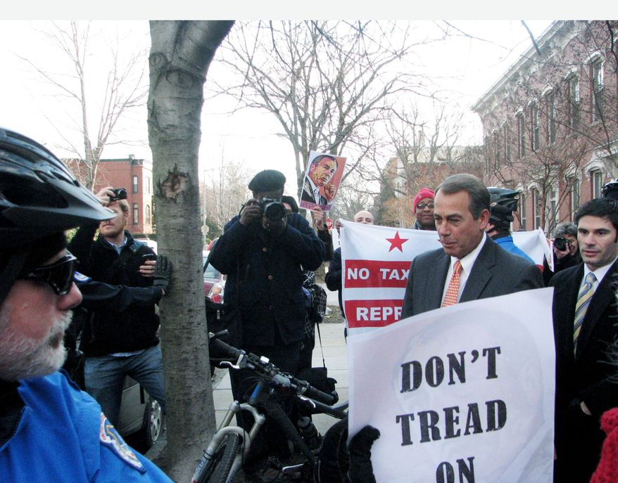 """House Speaker John A. Boehner, here surrounded by D.C. voting rights demonstrators, said Thursday, """"When we say we're going to cut spending, read my lips: We're going to cut spending."""" (PRNEWSFOTO/DC Vote)"""