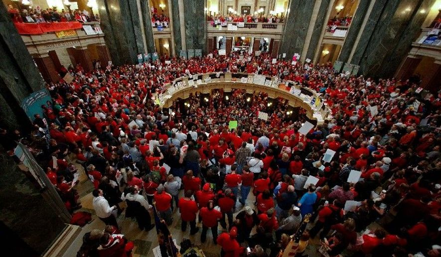 MAD IN MADISON: Opponents of Wisconsin Gov. Scott Walker's bill to sharply curtail state employees' collective-bargaining rights demonstrate in the Rotunda of the state Capitol in Madison on Thursday. Senate Democrats fled the state to prevent a quorum and a vote on the bill. (Associated Press)