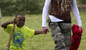 FILE - In this March 30, 2009 file photo, U.S. singer Madonna with adopted son David Banda visiting the Mphandula Day Care Centre for orphans near Lilongwe, Malawi. (AP Photo/Tsvangirayi Mukwazhi, file)