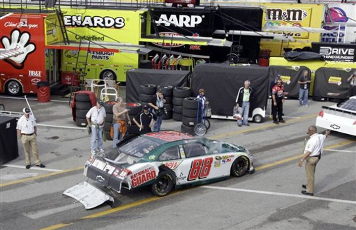 Dale Earnhardt, Jr., brings his damaged race car into the garage area after a crash during practice for Sunday's NASCAR Daytona 500 auto race at Daytona International Speedway in Daytona Beach, Fla., Wednesday, Feb. 16, 2011. (AP Photo/Lynne Sladky)