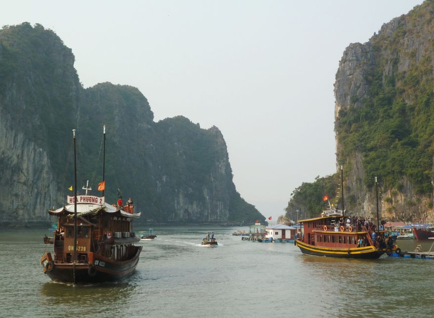 In this November 2010 photo, cruise boats make their way in Ha Long Bay near the Vietnam-China border in the Gulf of Tonkin. Early Thursday, Feb. 17, 2011, an overnight boat packed with sleeping tourists sank in the scenic bay, killing 12 foreigners, including vacationers from the United States, Australia and Britain, and their Vietnamese guide, officials said. (AP Photo/Kyodo News)