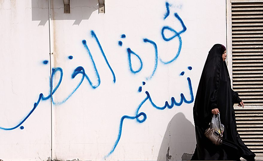 """A Bahraini anti-government demonstrator walks outside a hospital in Manama, Bahrain, early Thursday morning, Feb. 17, 2011, past writing in Arabic on the wall that reads: """" the revolution of rage contains."""" (AP Photo/Hasan Jamali)"""