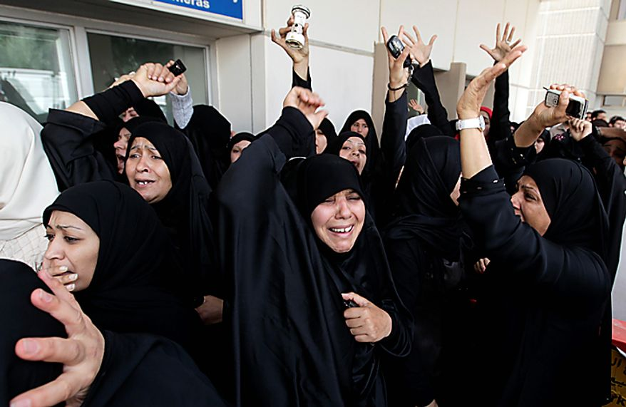 Women demonstrators shout anti-goverment slogans after riot police drove demonstrators from a main square in Manama, Bahrain, early Thursday morning, Feb. 17, 2011. Armed patrols prowled neighborhoods and tanks appeared in the streets for the first time Thursday after riot police with tear gas and clubs drove protesters from a main square where they had demanded sweeping political change in this tiny kingdom. (AP Photo/Hassan Ammar)