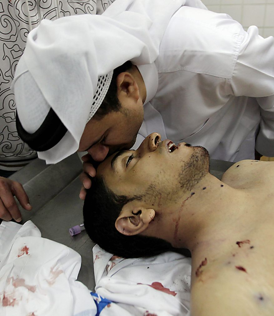 A man kisses the forehead of Ali Massour Khodier, who was killed during clashes between demonstrators and police in Manama, Bahrain, on Thursday, Feb. 17, 2011. Army patrols and tanks locked down the capital of this tiny Persian Gulf kingdom after riot police swinging clubs and firing tear gas smashed into demonstrators, many of them sleeping, in a pre-dawn assault Thursday that uprooted their protest camp demanding political change. Medical officials said four people were killed. (AP Photo)