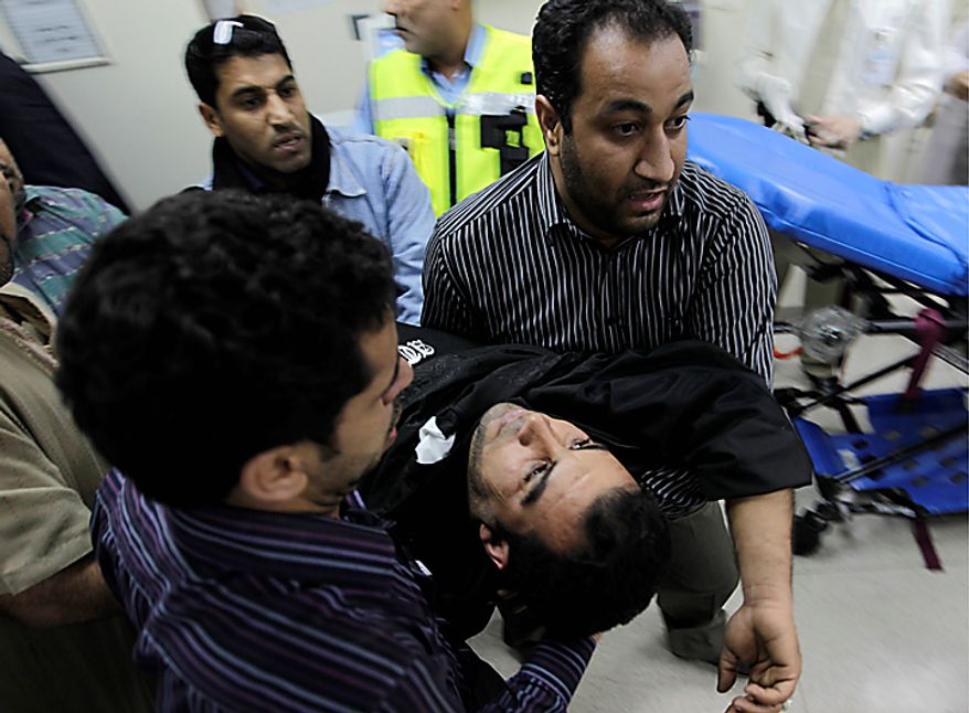 Bahraini anti-government demonstrators take an injured protester to a hospital in capital Manama early Thursday morning, Feb. 17, 2011. Armed patrols prowled neighborhoods and tanks appeared in the streets for the first time Thursday after riot police with tear gas and clubs drove protesters from a main square where they had demanded sweeping political change in this tiny kingdom. (AP Photo/Hassan Ammar)