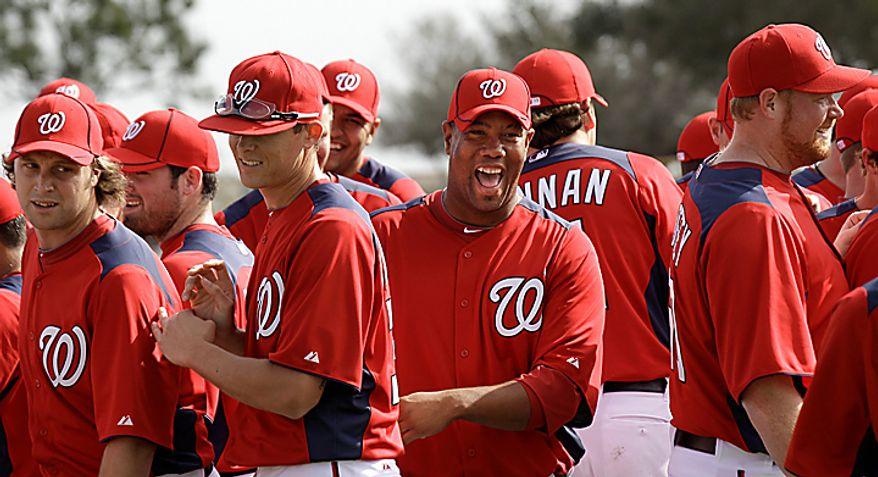 **FILE** Washington Nationals pitcher Livan Hernandez, center, laughs with teammates during a spring training baseball workout Thursday, Feb. 17, 2011, in Viera, Fla. (AP Photo/David J. Phillip)