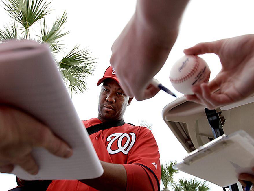 Washington Nationals starting pitcher Livan Hernandez signs autographs for fans after a spring training baseball workout Thursday, Feb. 17, 2011, in Viera, Fla. (AP Photo/David J. Phillip)