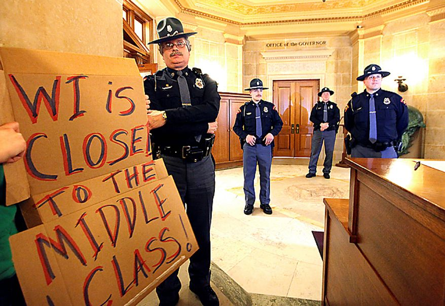 Wisconsin State Patrol officers are stationed outside the office of Gov. Scott Walker on Wednesday, Feb. 16, 2011, in Madison, Wis., as thousands of demonstrators swarm the state Capitol, including a protester holding a sign, for a second day of protests. (AP Photo/Wisconsin State Journal, John Hart)