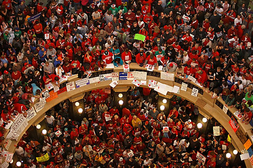 Demonstrators against Wisconsin Gov. Scott Walker's bill to eliminate collective bargaining rights for many state workers pack the Rotunda of the state Capitol in Madison, Wis., on Thursday, Feb. 17, 2011. (AP Photo/Andy Manis)