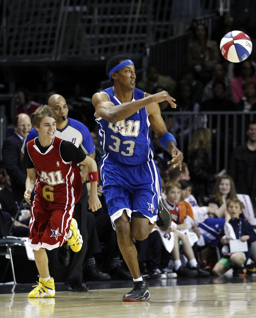 Former NBA basketball player Scottie Pippen, center, and singer Justin Bieber make their way down the court during a NBA All-Star celebrity basketball game in Los Angeles, Friday, Feb. 18, 2011. (AP Photo/Jae C. Hong)