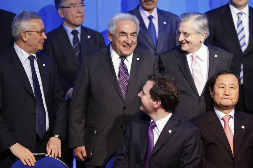 European Central bank President Jean Claude Trichet, right, looks at International Monetary Fund (IMF) Managing Director Dominique Strauss-Kahn, center, during the family picture of the G-20 Finance summit at Bercy Finance Ministry in Paris, Saturday, Feb. 19, 2011. Finance chiefs from the world's 20 industrialized and fastest developing nations wrestle over how to steady the world economy at a two-days meeting in Paris. (AP Photo/Francois Mori)